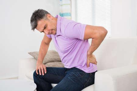 Älterer Mann, die Rückenschmerzen beim Sitzen auf dem Sofa