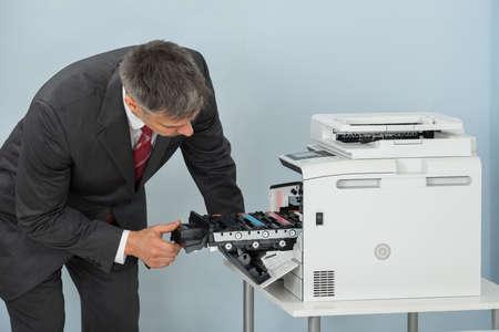 fotocopiadora: El hombre de negocios maduro fijación de cartucho en la máquina impresora En La Oficina