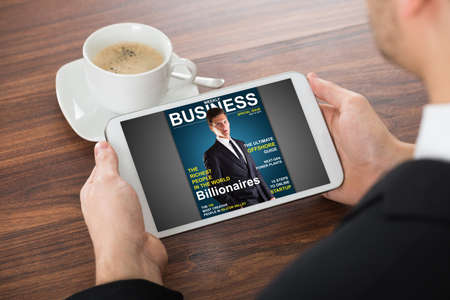 digital media: Businessman Reading Online Magazine On Digital Tablet With Cup Of Tea On Desk