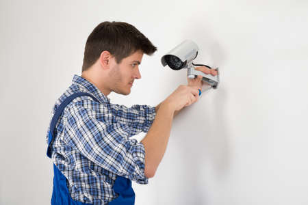 Close-up Of Technician Adjusting CCTV Camera On Wall