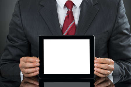 blank tablet: Closeup Of Businessman Showing Tablet With Blank Screen At Desk Stock Photo