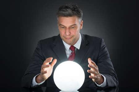soothsayer: Retrato de hombre de negocios predicción de futuro con la bola de cristal en el escritorio