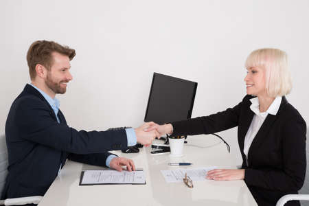 businesspeople: Two Young Happy Businesspeople Shaking Hands In Office Stock Photo