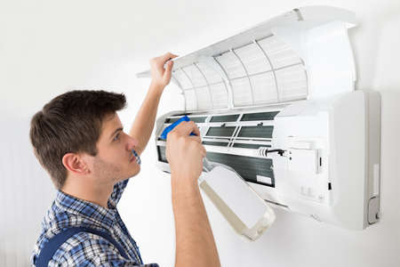 condition: Young Male Technician Cleaning Air Conditioner At Home Stock Photo