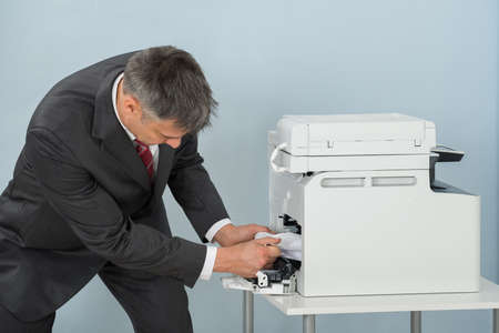 Businessman Bend Down To Remove Paper Stuck In Printer At Office Stock Photo