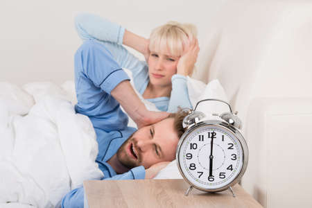 awakened: Exhausted Young Couple Awakened By Alarm Clock In Bedroom At Home