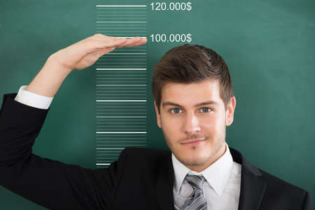 measuring: Rear View Of A Young Businessman Measuring Profit