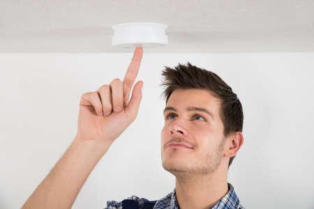 in the smoke: Hombre joven electricista Prueba Detector de humo en el hogar