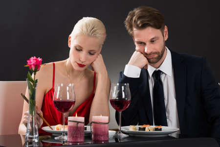 Portrait Of A Sad Couple Having Dinner At A Restaurant With Black Background
