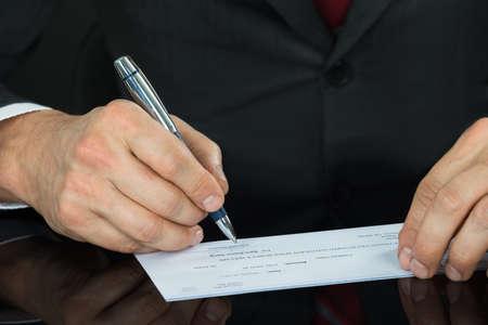 chequera: Primer plano del hombre de negocios Mano de llenado de cheques en blanco en el escritorio Foto de archivo