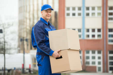 carrying: Mature Happy Delivery Man Carrying Cardboard Box Stock Photo