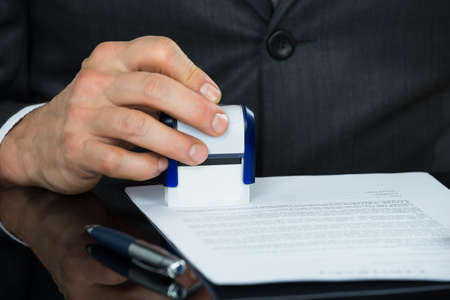 envelopes: Close-up Of Businessman Stamping Document At Desk Stock Photo