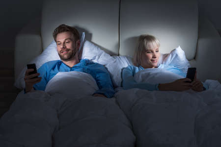 bedcover: Young Happy Couple Lying In A Bed Holding Mobile Phones At Home Stock Photo