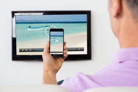 wifi: Mature Man With Smartphone Connected To A TV Watching Video At Home