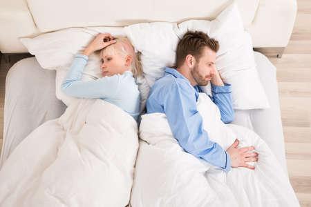 asleep: High Angle View Of Sad Couple Lying On Bed At Home