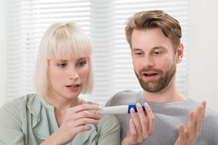 stress testing: Close-up Of Shocked Couple Sitting On Sofa Looking At Pregnancy Tester At Home