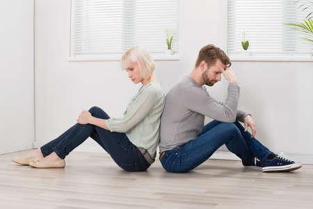 mujer triste: Triste pareja de jóvenes sentados espalda con espalda en el suelo en casa