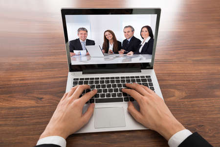 Close-up Of Businessman Video Conferencing On Laptop At Desk In Office photo