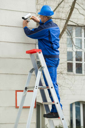 stepladder: Mature Male Technician Standing On Stepladder Fitting CCTV Camera On Wall Stock Photo
