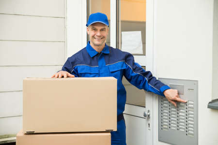 intercom: Delivery Man Using Intercom To Enter Home For Delivery