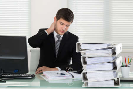 INVOICE: Businessman Suffering From Neckache With Invoice On Desk