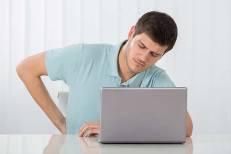 relieving pain: Young Man Suffering From Backache While Working On Laptop Stock Photo