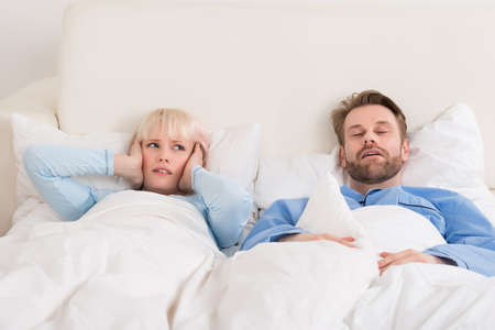 snoring: Young Woman Covering Ears While Man Snoring In Bed At Home
