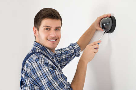 surveillance camera: Young Male Technician Installing Surveillance Camera On Wall Stock Photo