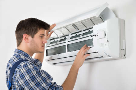 man in air: Photo Of Young Male Technician Repairing Air Conditioner Stock Photo