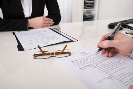 interview: Close-up Of Businessperson With Resume And Pen In Office Stock Photo