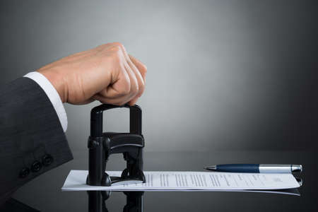 signing authority: Close-up Of Businessman Hand Stamping Contract Document At Office Desk Stock Photo