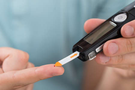 disease patients: Close-up Of Young Man Hand Using Glucometer To Check Blood Sugar Level Stock Photo