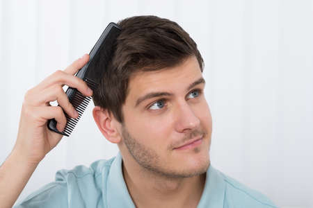 comb hair: Close-up Of Young Man Combing His Hair With Comb Stock Photo