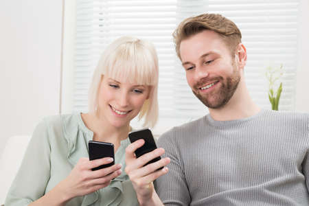 couple on couch: Young Happy Couple Sitting On Couch Using Cellphone
