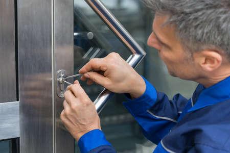中年の男性 Lockpicker の自宅のドアのハンドルを固定 写真素材