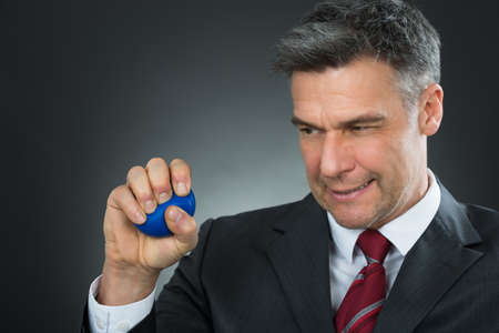 muscle tension: Businessman Pressing Stressball In Hand Over Black Background Stock Photo
