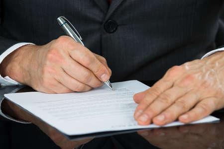 Primer plano del hombre de negocios Mano que sostiene la pluma de la forma sobre el Contrato en el escritorio