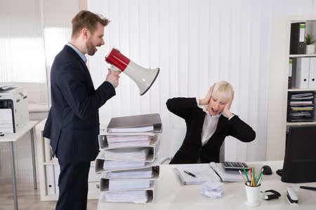 workplace harassment: Protuberancia que grita Al joven empresaria a través del altavoz En Office Foto de archivo