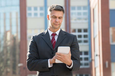 networking people: Happy Businessman Holding Digital Tablet Outside Office Building Stock Photo