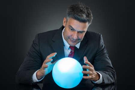 Portret Van Zakenman Het voorspellen van de toekomst met kristallen bol op Bureau