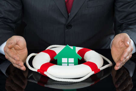 sheltering: Close-up Of Businessman Hand Sheltering House With Lifebuoy At Desk