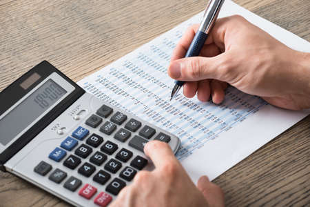 合計: Close-up Of A Businessman Analyzing Accounting Document With Calculator At Desk In Office