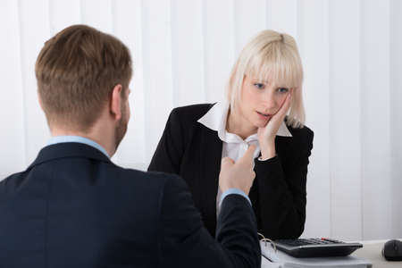 blaming: Close-up Of Boss Blaming Young Female Employee For Bad Results In Office Stock Photo
