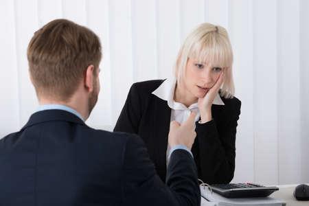 acoso laboral: Primer Del Jefe de culpar Mujer joven empleado de malos resultados en oficina