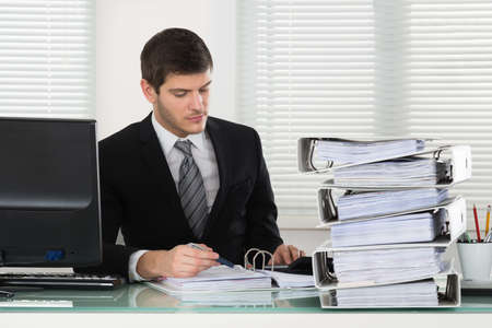 stack of papers: Photo Of Young Businessman Calculating Invoice In Office