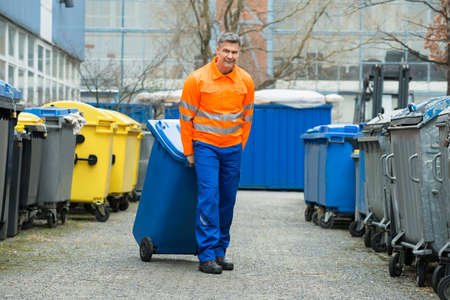 collectors: Happy Male Worker Walking With Dustbin On Street During Day Stock Photo