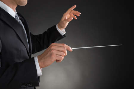 choral: Person Directing With A Conductors Baton On Grey Background
