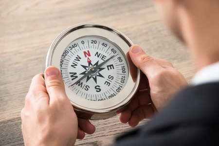 guiding: Close-up Of Young Businessman Holding Compass At Desk In Office