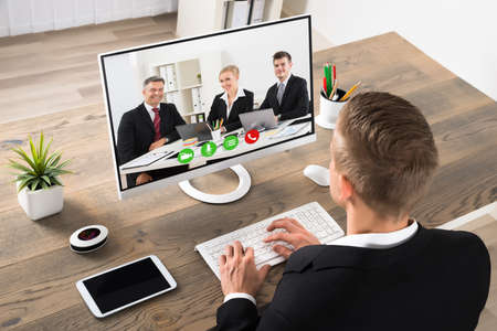 El hombre de negocios joven Asistir Videoconferencia En El Ordenador En Oficina