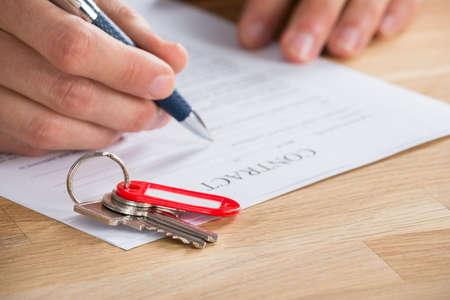 llaves: Primer plano de la mano de negocios Firma de contrato con las llaves en Es Foto de archivo